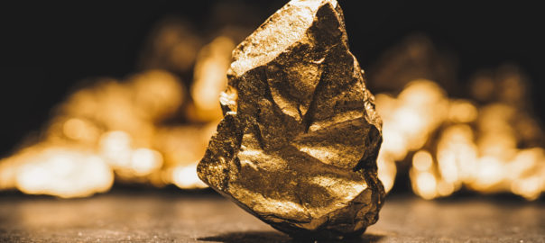 big gold nugget in front of a mound of gold